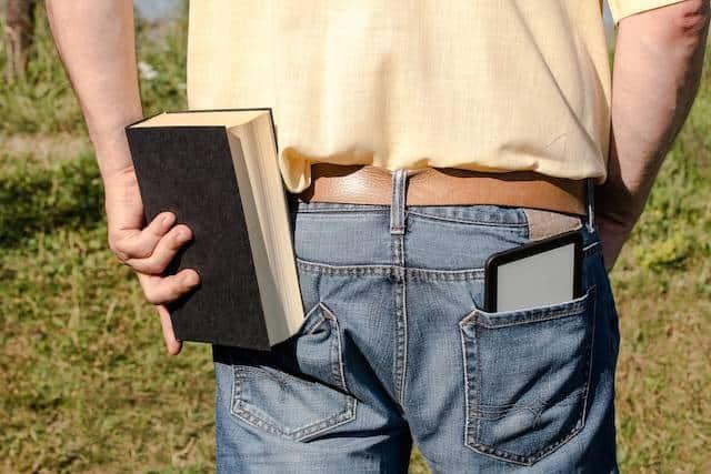 Sony Reader PRS-T2, Kindle Paperwhite und Buch in der Sonne